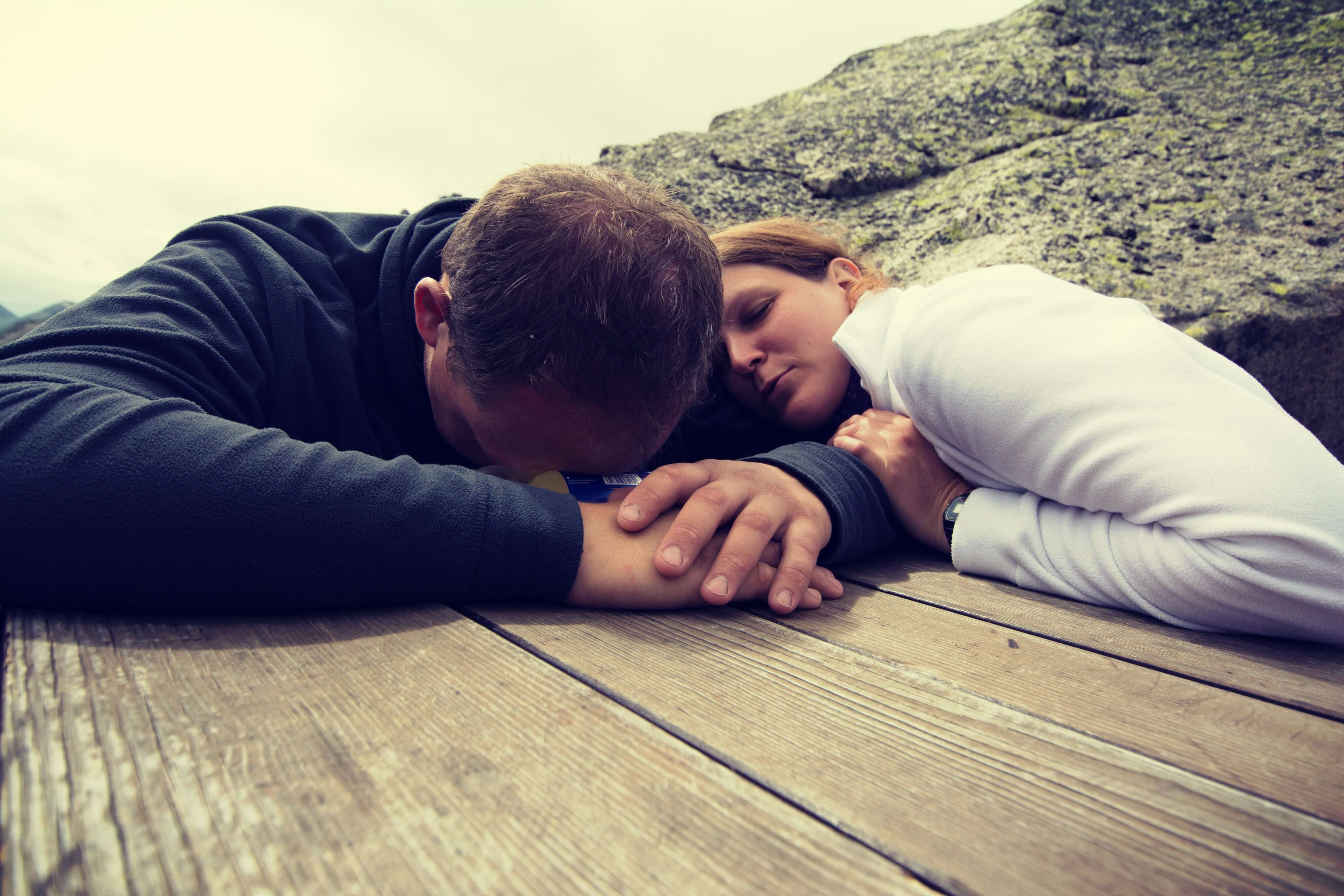 Hannah und ihr Freund erschöpft auf einem Tisch in den Bergen bei der Recherche zu Barfuß auf Wolken