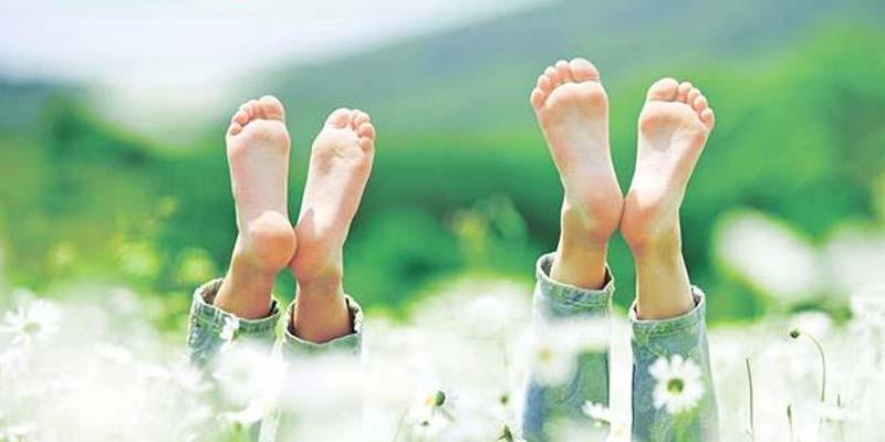 Ein Pärchen liegt in einer Blumenwiese und streckt die nackten Füße in den Hblauen Himmel - Barfuß durchs Leben halt.